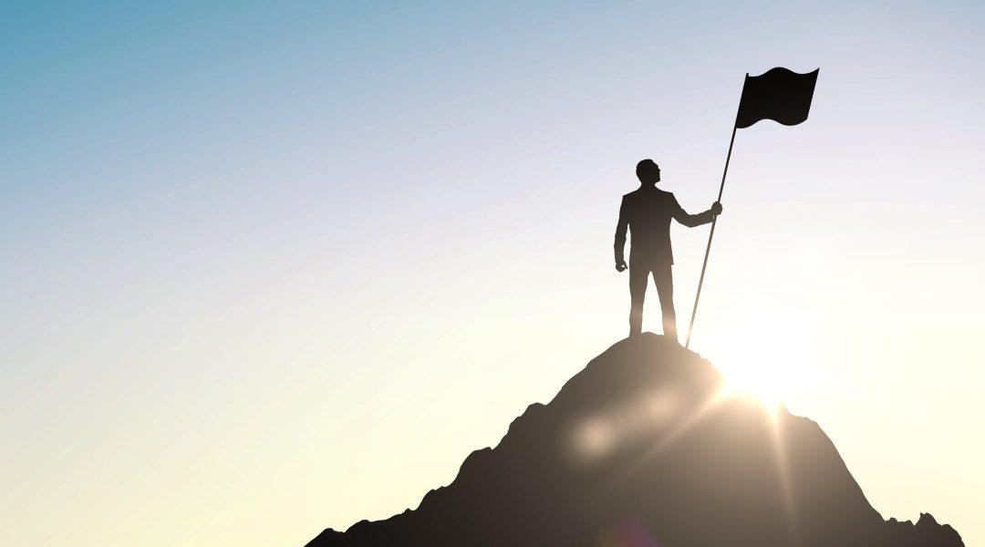 Person som håller i flagga på bergstopp