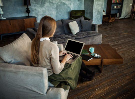 Kvinna som sitter i fåtölj med laptop