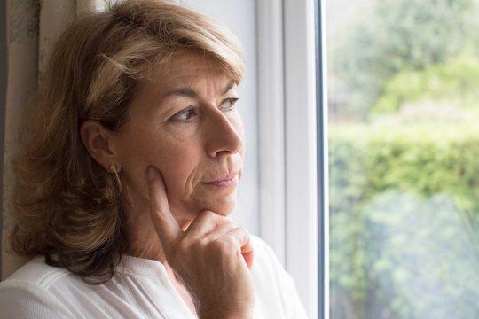 Kvinna som tittar ut genom fönster