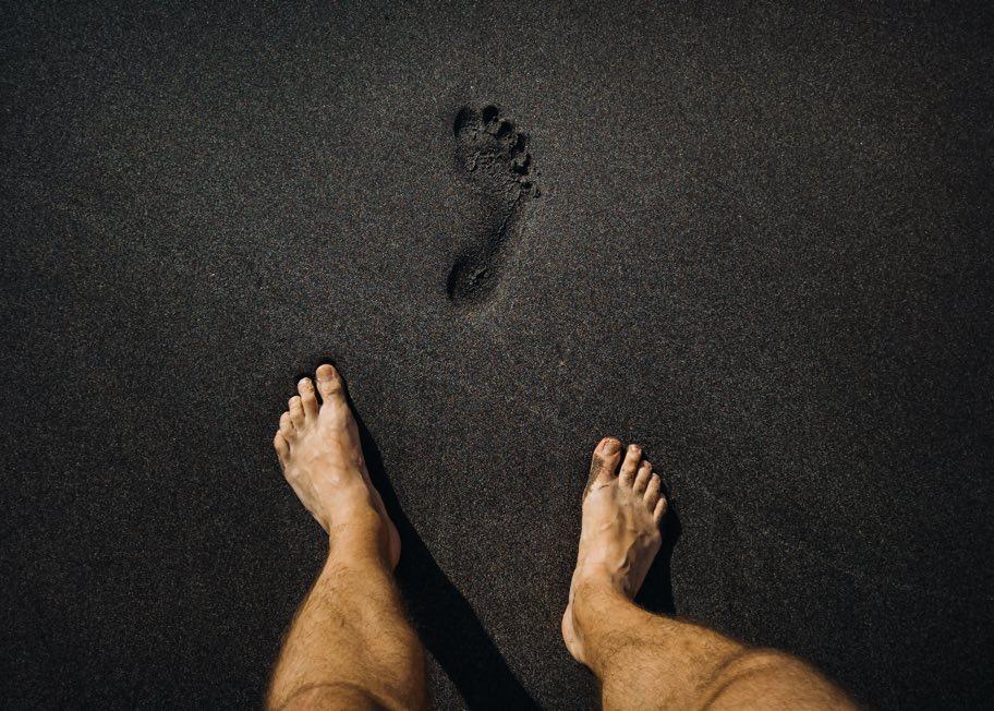 Fotavtryck i svart sand